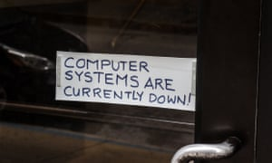 A sign referring to the hacked computer system of Baltimore City is taped to a door near Baltimore City Hall in Baltimore, Maryland