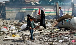 A boy walks through ruins in Sana'a