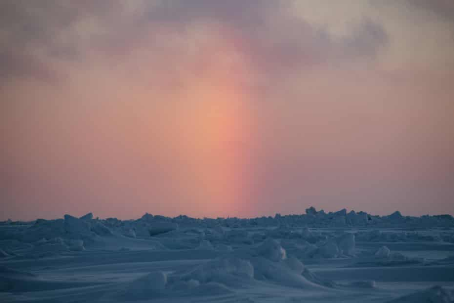 An unusual phenomenon known as a sun pillar forms between above the sea ice on the Chukchi Sea. This type of refraction is only seen when the air is filled with ice crystals.
