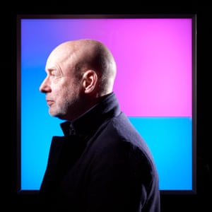 Brian Eno, in profile, wearing a jacket with a turned-up collar