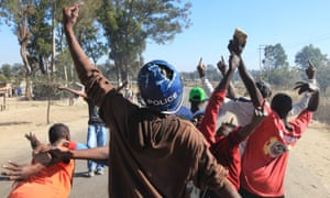 A young man wearing a police helmet joins angry protestors in Harare, 4 July.