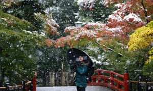A visitor takes a photo in the snow at the Tsurugaoka Hachimangu shrine in Kamakura.