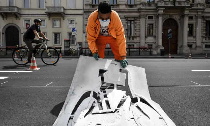 A worker paints signs for a new cycle path in central Milan.