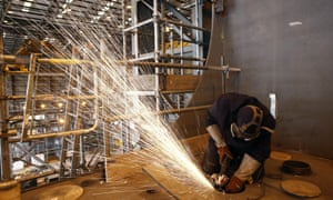 A worker grinds metal inside a section of the British Royal Navy's new HMS Prince of Wales aircraft carrier