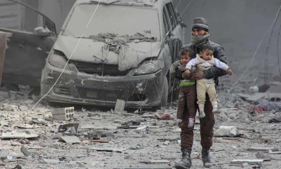 A man carries two young boys through a heavily damaged street in Arbin, eastern Ghouta