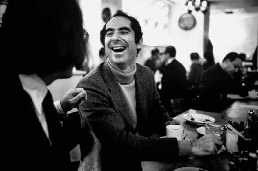 Philip Roth sitting at lunch counter in Newark, New Jersey in 1968, talking to a customer.