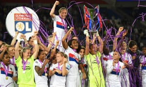 Match winning goalkeeper Sarah Bouhaddi lifts the trophy as her team-mates celebrate Lyon's fourth European victory.