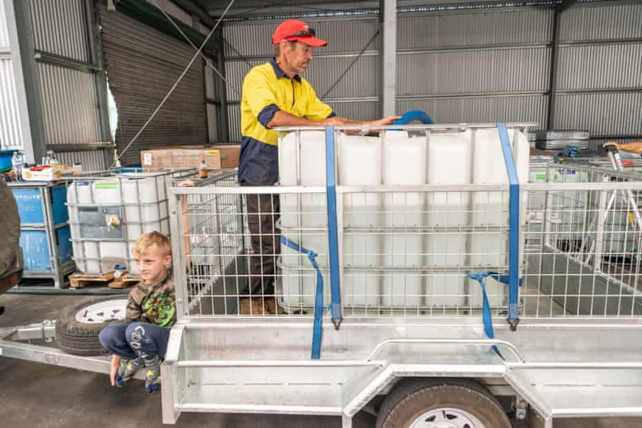 Les Watnell and son Noah Balaam refill the family drinking water pod at the Granite Belt water relief station