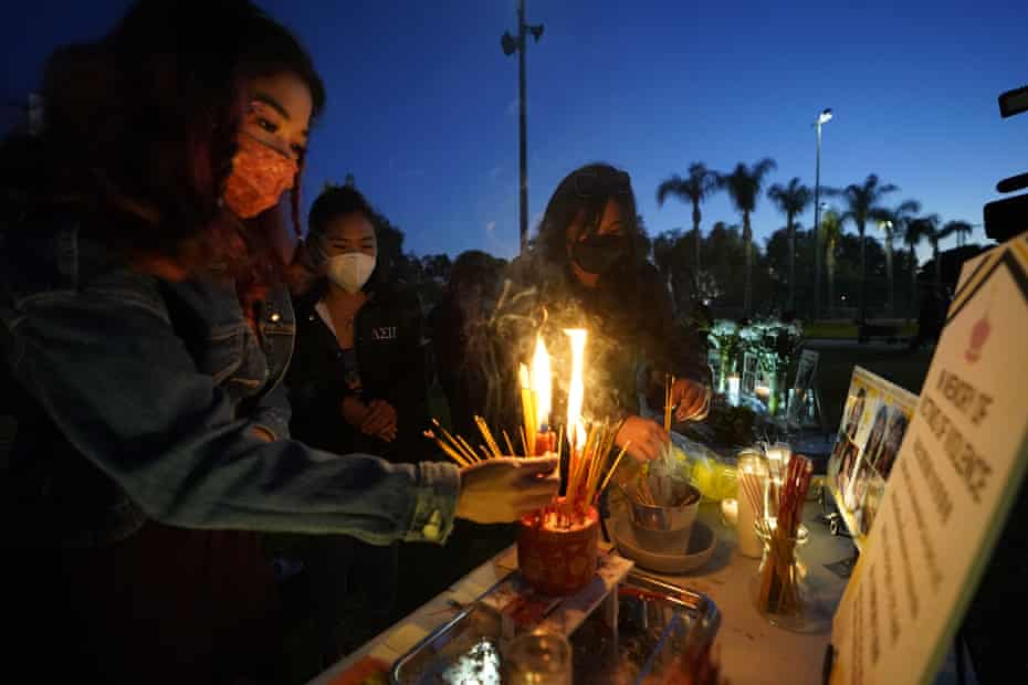 Women pay theirs respects at a memorial in honor of the victims of the shootings in Atlanta, where eight people, including six Asian American women, were killed the week before, during a candle vigil in Monterrey Park, California, on 27 March.