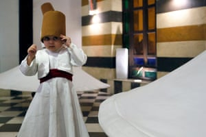 Damascus, Syria. Three-year-old Sufi dervish dancer Anas al-Kharrat dances with his family members at a restaurant in the Shahgur district of the old city of Damascus. The Kharrat family are one of several trying to preserve the Sufi whirling ritual