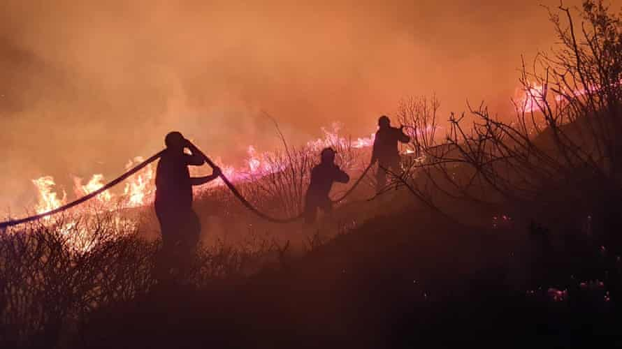 A volunteer with the Greek fire service tackles a wildfire in near Athens.