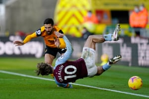Wolves' Joao Moutinho collides with Jack Grealish.
