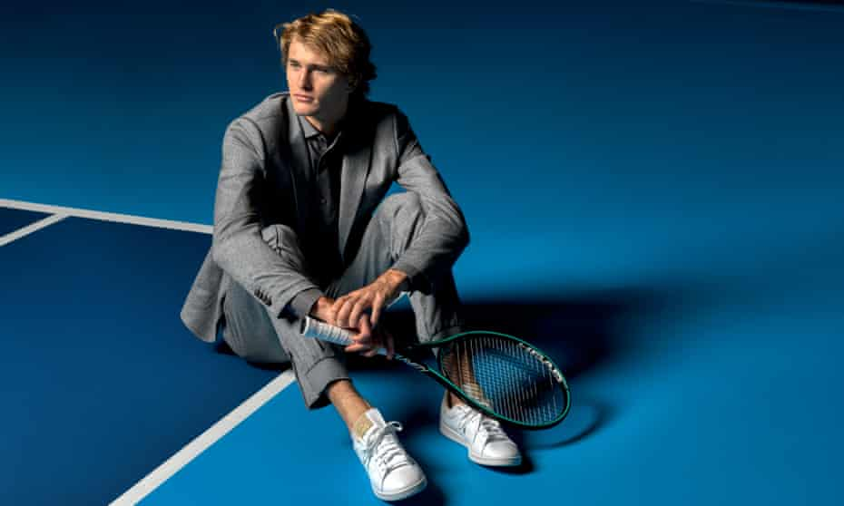 Alex Zverev in a shiny grey smart-casual suit and shirt, and white trainers, holding a racquet, sitting on the edge of a tennis court.