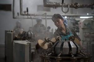 Pyongyang, North Korea: A worker operates machinery at a silk mill
