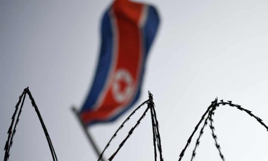 The North Korean flag is seen flying in backdrop of barbed wire