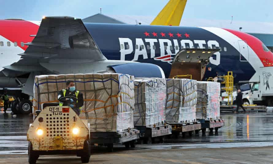 Workers unload a jet used by the New England Patriots after it landed at Logan Airport from Shenzhen, China with a shipment of over one million N95 masks.