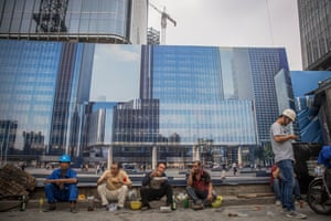 Chinese migrant workers resting outside a construction site during lunch time in the central business district of Beijing today.