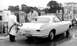 Roger Moore watches a garage attendant fill The Saint's trademark Volvo with petrol in 1962