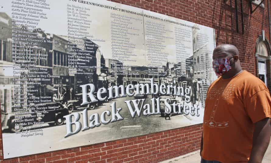 Freeman Culver stands in front of a mural listing the names of businesses destroyed during the Tulsa race massacre in Tulsa, Oklahoma.