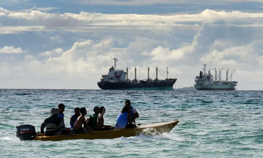 Local fishermen in Tuvalu with a foreign fishing vessel in the background