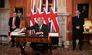 Boris Johnson signing the trade deal, with David Frost (left), the UK's chief negotiator, and Sir Tim Barrow, its ambassador to the UK (right) looking on.