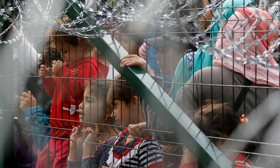 Refugees stand behind the fence in Serbia at the closed border with Hungary.