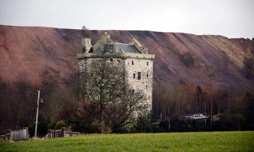 Niddry Castle, near Winchburgh, with a large oil shale behind, in Scotland, UK.