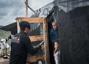 A member of the Moria Corona Awareness Team distributes an information leaflet to inhabitans of the Moria refugee Camp on Lesbos, Greece, in May 2020.