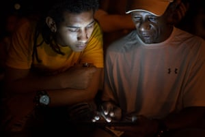 Two men log in an ETECSA wi-fi hotspot in Parque Fe del Valle