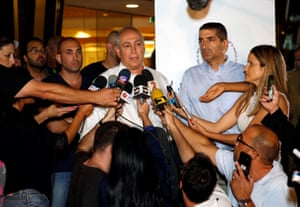 A man surrounded by journalists with microphones
