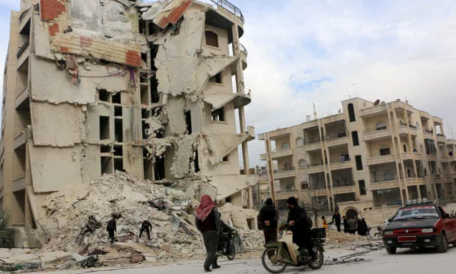 Civil defence workers search a ruined building after an airstrike in Idlib city centre on Monday.