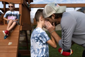 Mark whispers to Joey while Jackson sits on the playset in the backyard in New Lenox, IL on November 8, 2020.