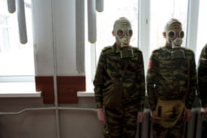 Cadet drills at School #7, Dmitrov, Russia.As part of a cadet course, students stand ready as a teacher observes how quickly they can dress in gas masks, 4 Apr 2016, School #7, Dmitrov, Russia.