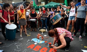 A demonstrator paints a slogan on the street in demand of women's access to safe, free and legal abortion, during a rally outside the national congress in Buenos Aires, on Tuesday.