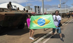 Bolsonaro supporters hold up a Brazilian flag in front of a tank as army soldiers take part in security preparations for the 1 January 1 inauguration ceremony.