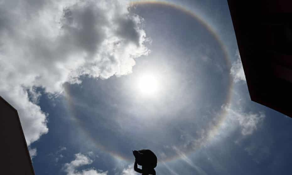 A halo forms around the sun above a statue in Singapore. The halo is formed when light from the sun or moon passes through ice crystals suspended in the upper atmosphere.