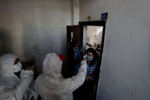 A worker in a protective suit measures the body temperature of a woman during a door-to-door inspection of residents following the spread of the coronavirus in Wuhan.