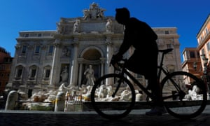A cyclist passes the Trevi fountain in Rome