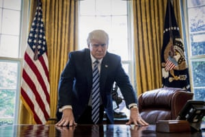 President Donald Trump poses for a portrait in the Oval Office in Washington.