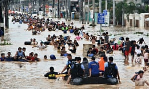 People wade in the chest deep floodwater in suburban Cainta, east of Manila, Philippines, in 2009. Such events will affect twice as many people by the end of the decade.