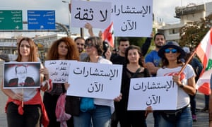 Protesters carry a Lebanese flag and placards as they block the road to the presidential palace in east Beirut on 1 November.