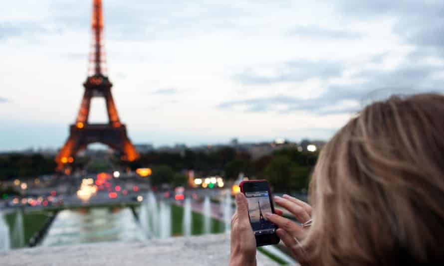 A woman takes a photo of the Eiffel Tower.