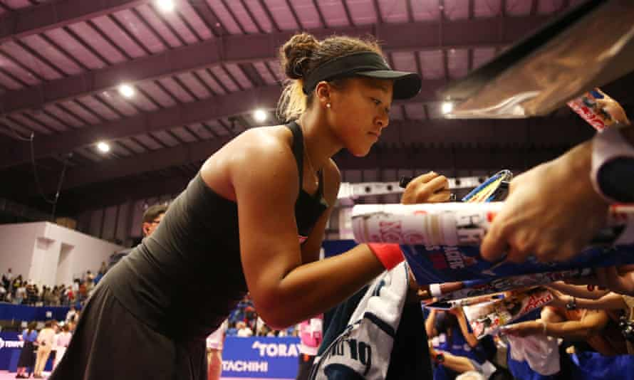 Naomi Osaka signs autographs for fans after her victory over Dominika Cibulkova at the Pan Pacific Open