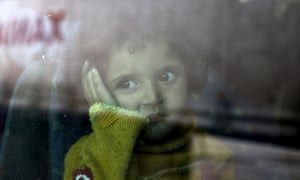 A Syrian child sits in a bus after arriving at the port of Piraeus, Greece, last week.