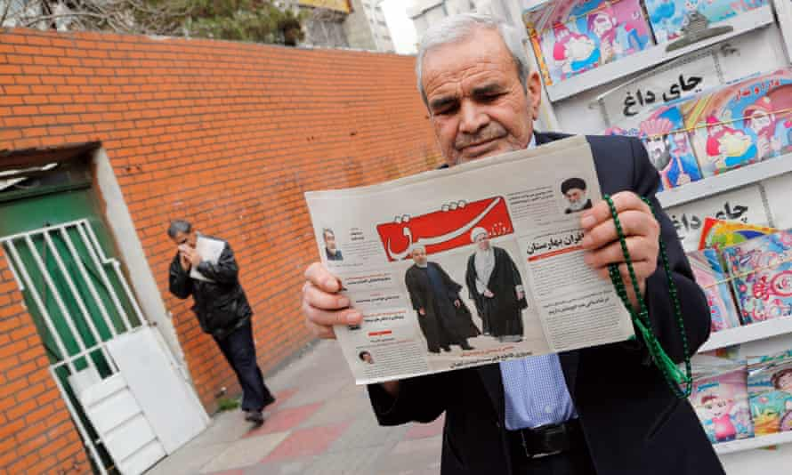 A man holds a copy of the daily Shargh newspaper with pictures of Iranian President Hassan Rouhani and former president Akbar Hashemi Rafsanjani.