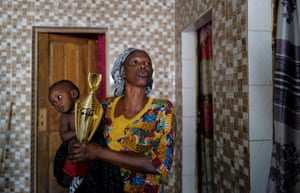 Diop's mother, Ndeye Boye, carries her son's Fair Play award. Adorned with colourful ceramic tiles on a busy back street, the house Diop shares with 12 family members is getting a new roof thanks to the money from his winnings