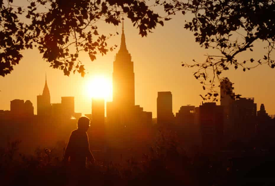 sun rises behind empire state building