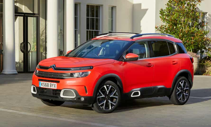 Citroen C5 Aircross red parked against white buildings