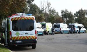 Medical transport vehicles line up at a Melbourne aged care home