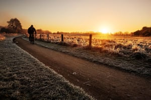 A man rides his bike at sunrise at Holme Pierrepont, Nottinghamshire